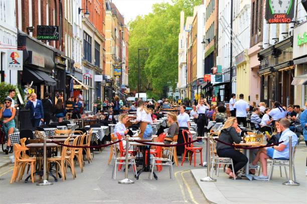 Bar and restaurant outdoor street seating in Soho, London London, United Kingdom - August 21 2020: Social distancing bar and restaurant outdoor street seating in Soho with crowd of people outdoor dining UK stock pictures, royalty-free photos & images