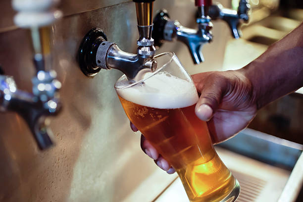 Bar Beer Tap with African American Person's Hand Filling Glass An African American person's hand filling a beer glass at a bar. pilsner stock pictures, royalty-free photos & images