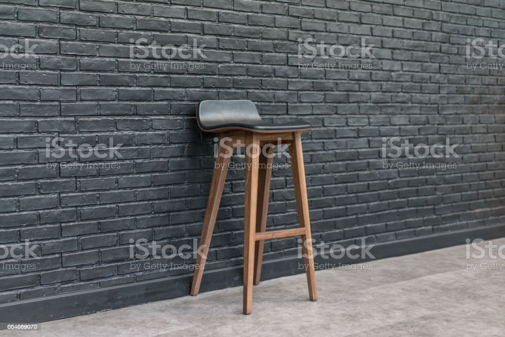Bar chair. Wood and leather seat on brick wall background, design concept stock photo