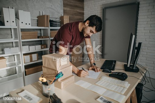 Delivery person preparing bar codes for packages, checking to do list