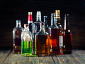 Group of various bottles of alcohol on the wooden bar counter