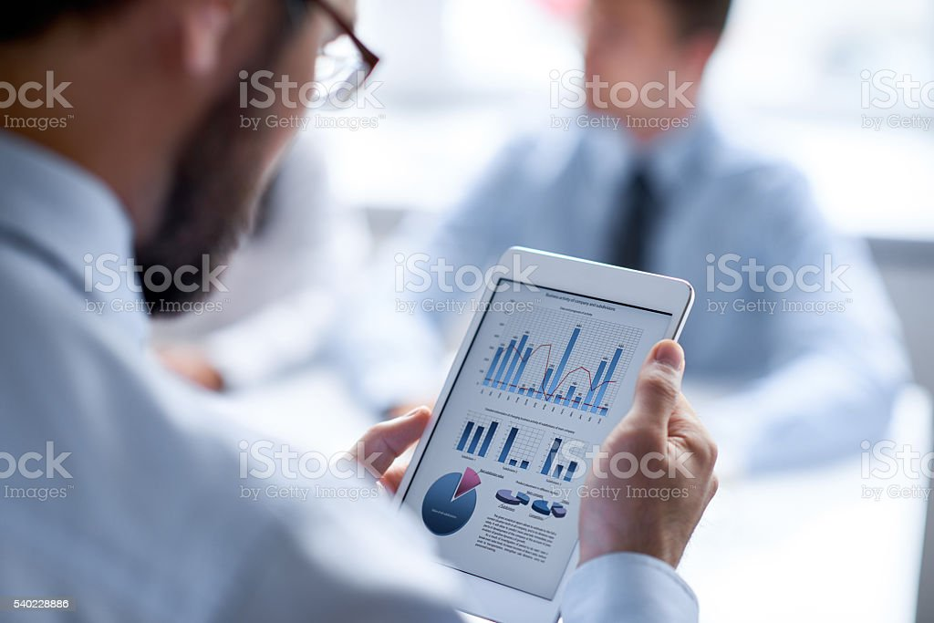 Bar graph and pie chart on tablet stock photo