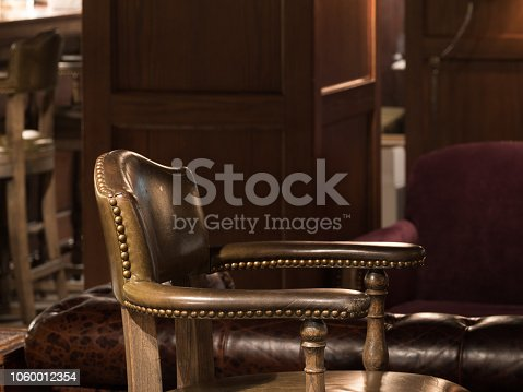 1044304084 istock photo Bar Interior Design In Classic Vintage Style. Comfortable Chair With Leather Upholstery And Cooper Rivets. Luxury Interior. Great Place For Relax After Work. 1060012354