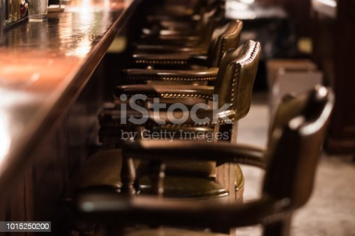 1044304084 istock photo Bar Interior Design In Classic Vintage Style. Oak Wooden Bar Counter, Comfortable Chairs With Leather Upholstery And Cooper Rivets. Luxury Interior. Great Place For Relax After Work. 1015250200