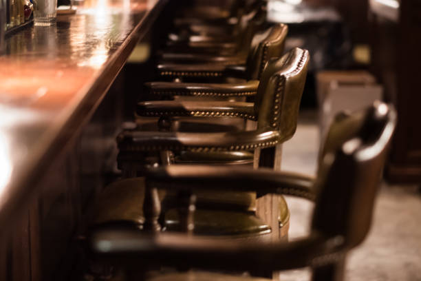 Bar Interior Design In Classic Vintage Style. Oak Wooden Bar Counter, Comfortable Chairs With Leather Upholstery And Cooper Rivets. Luxury Interior. Great Place For Relax After Work. Bar, Interior, Design, Classic, Luxury saloon stock pictures, royalty-free photos & images