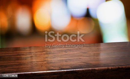 1044304084 istock photo bar nightclub background.Empty diagonal brown wooden table with blur bar restaurant bokeh lights,banner mockup template for display of product 1226723829