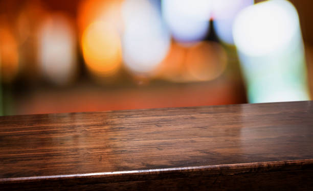 bar nightclub background.Empty diagonal brown wooden table with blur bar restaurant bokeh lights,banner mockup template for display of product stock photo