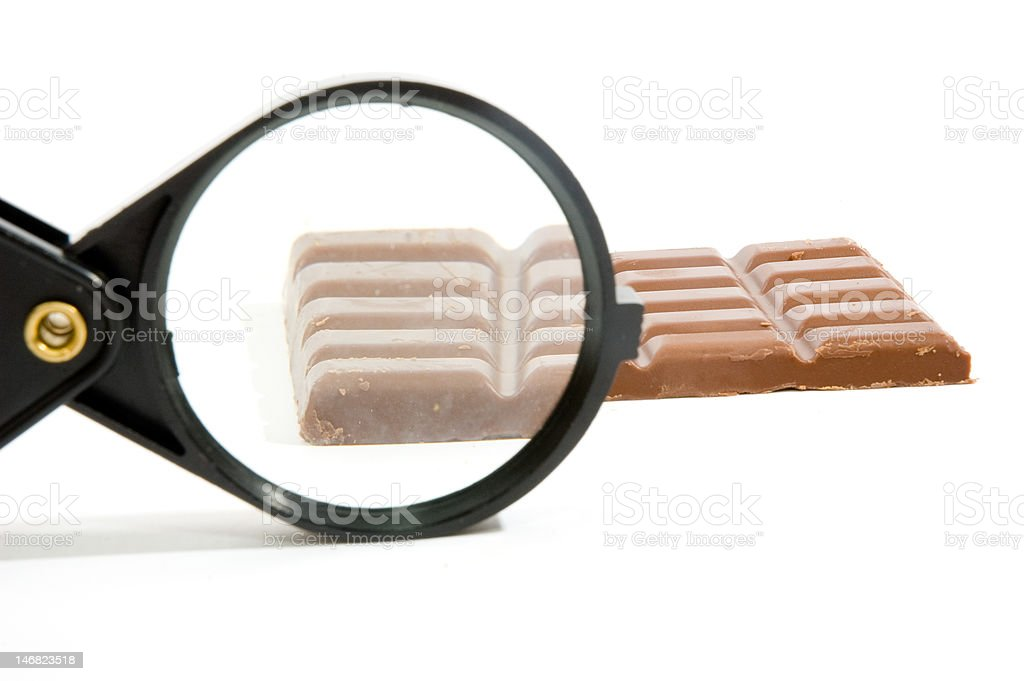 bar of chocolat sized up by a magnifying-glass stock photo