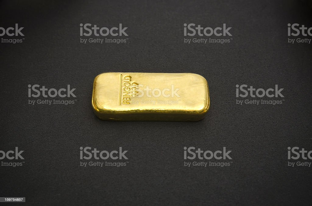 Barra de ouro em um fundo preto - foto de acervo