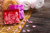 Bar of natural handmade soap with towel on wooden background