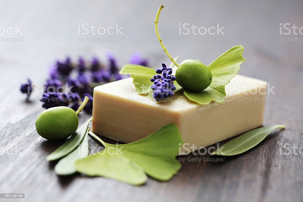 Bar of soap surrounded by berries, leaves, and lavender stock photo