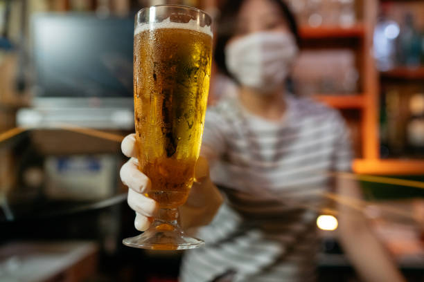Bar owner serving beer with protective plastic glove from behind protective plastic curtain stock photo