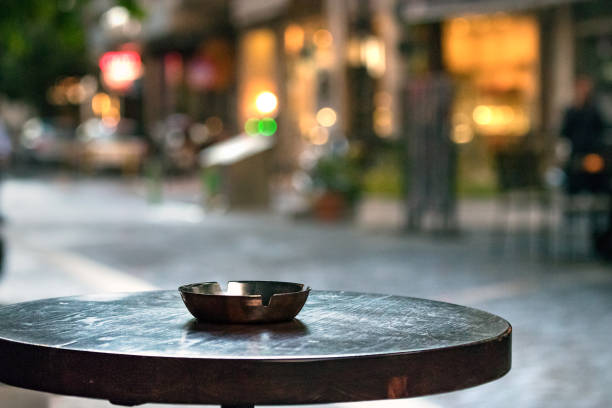A bar round wooden table with an ashtray, outdoors in the evening, copy space. stock photo
