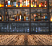 istock Bar with blurred lights bokeh and wooden table Bar with blurred lights bokeh and wooden table 1182304775