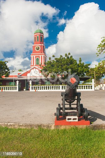 Famous red clock tower on the main guardhouse at the Garrison Savannah with old cannons in front of it. UNESCO garrison historic area Bridgetown, Barbados