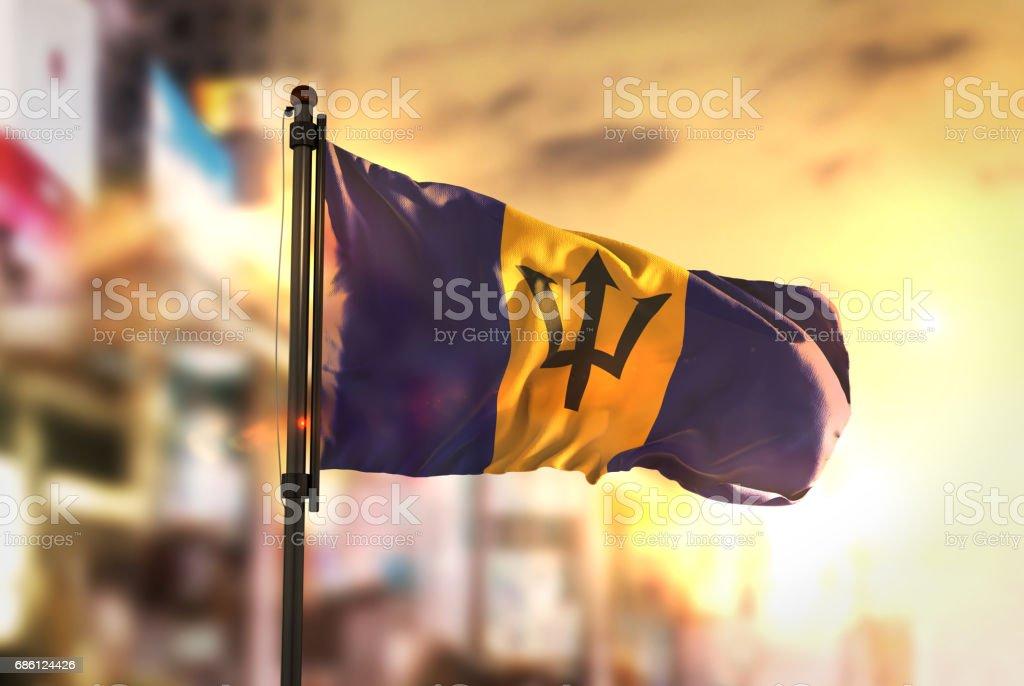 Bandeira de Barbados contra cidade turva fundo no Sunrise Backlight - foto de acervo