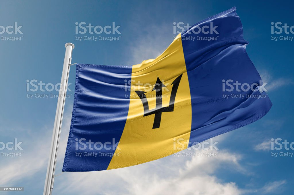 Barbados Flag is Waving Against Blue Sky stock photo