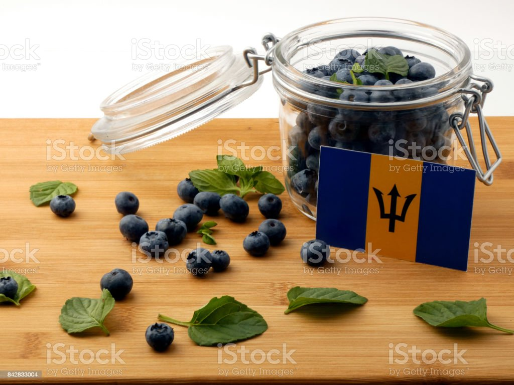 Barbados flag on a wooden plank with blueberries isolated on white stock photo