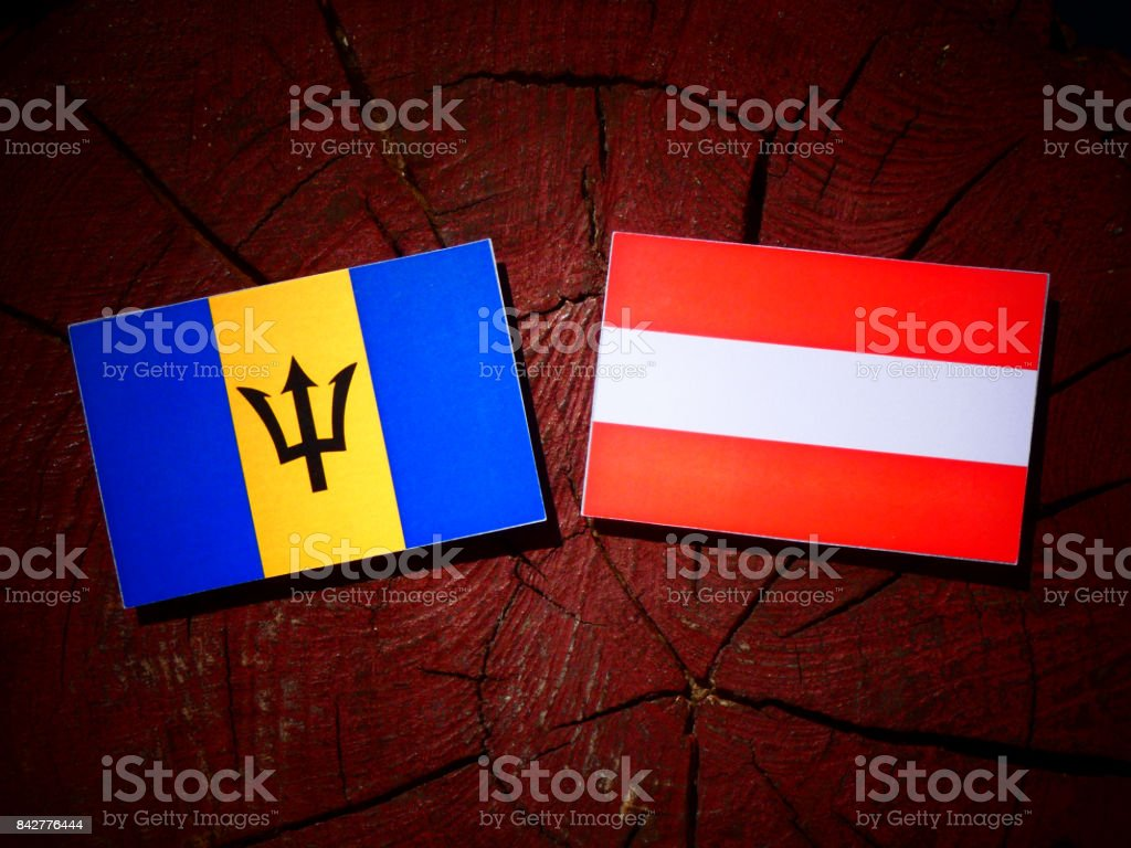 Barbados flag with Austrian flag on a tree stump isolated stock photo