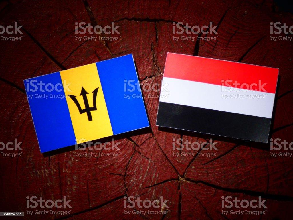 Barbados flag with Yemeni flag on a tree stump isolated stock photo