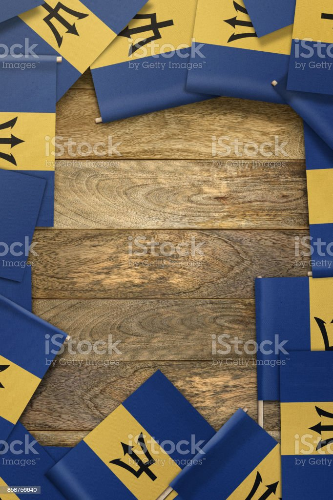 Barbados small flags framing a wood texture background with copy space stock photo