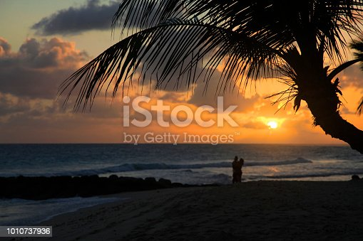 Romantic couple at beach with sunset in the background at Barbados island