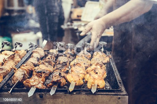barbecue and the hand of the man who cooks it. Preparation of meat slices in sauce on fire