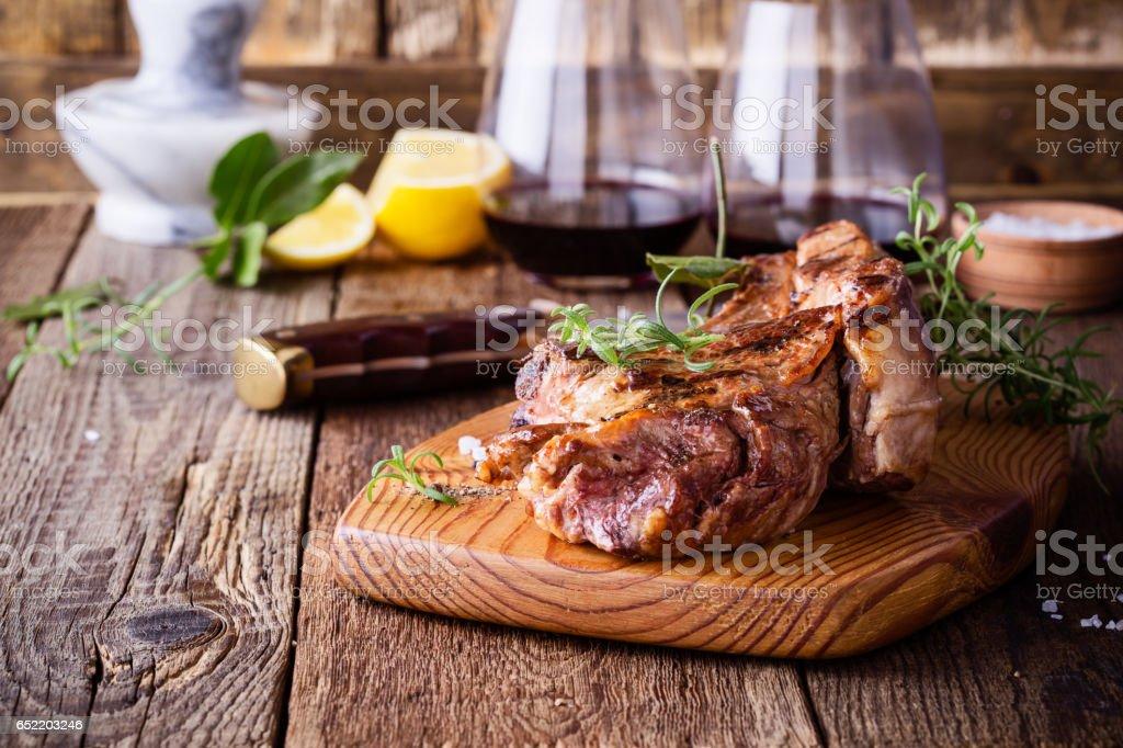 Barbecue bone ribeye steak on rustic cutting board stock photo