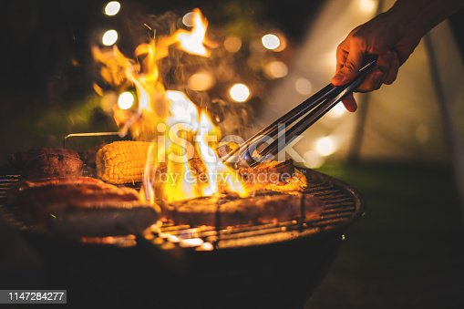 Family making barbecue in dinner party camping at night