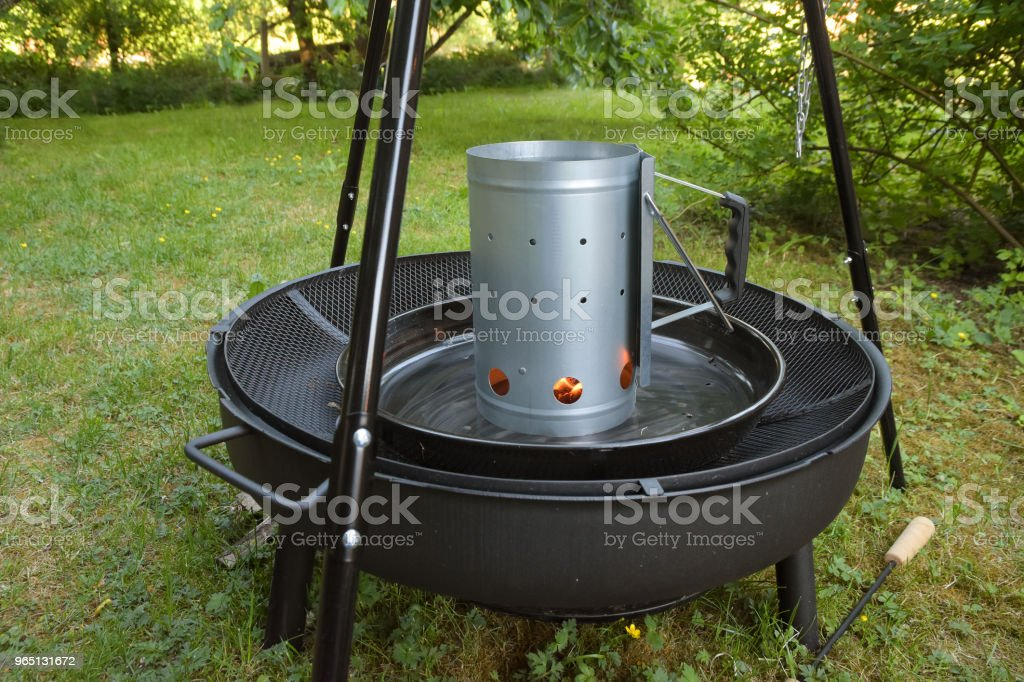 Barbecue charcoal chimney starter on a black tripod swivel grill in the garden royalty-free stock photo