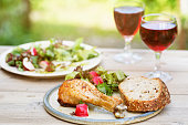 Barbecue chicken drum sticks picnic  with bread and red wine