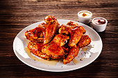 Chicken wings and vegetables on wooden table