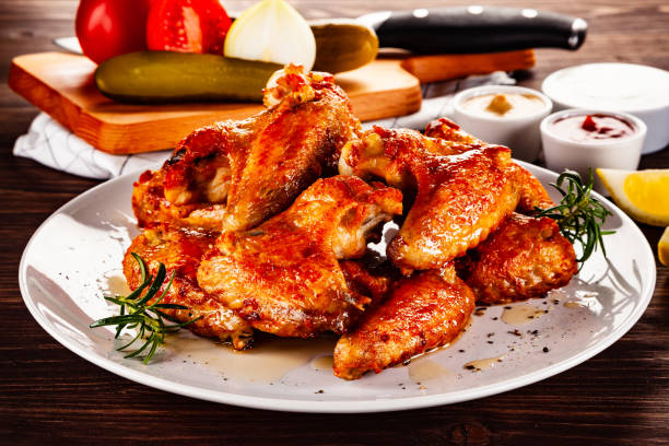 Barbecue chicken wings and vegetables on wooden table