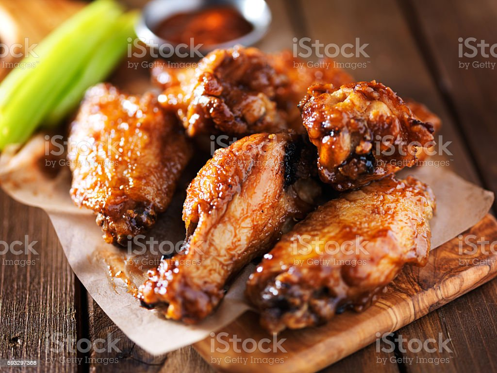 barbecue chicken wings close up on wooden tray barbecue chicken wings close up on wooden tray shot close up Appetizer Stock Photo
