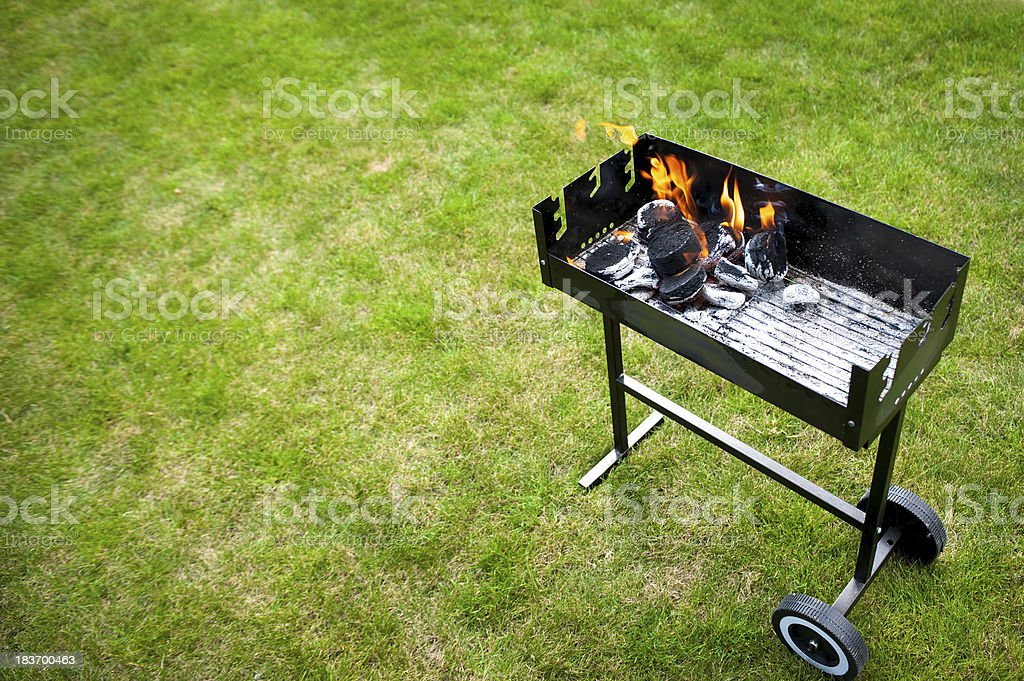 Barbecue fire on wheels against green lawn. royalty-free stock photo