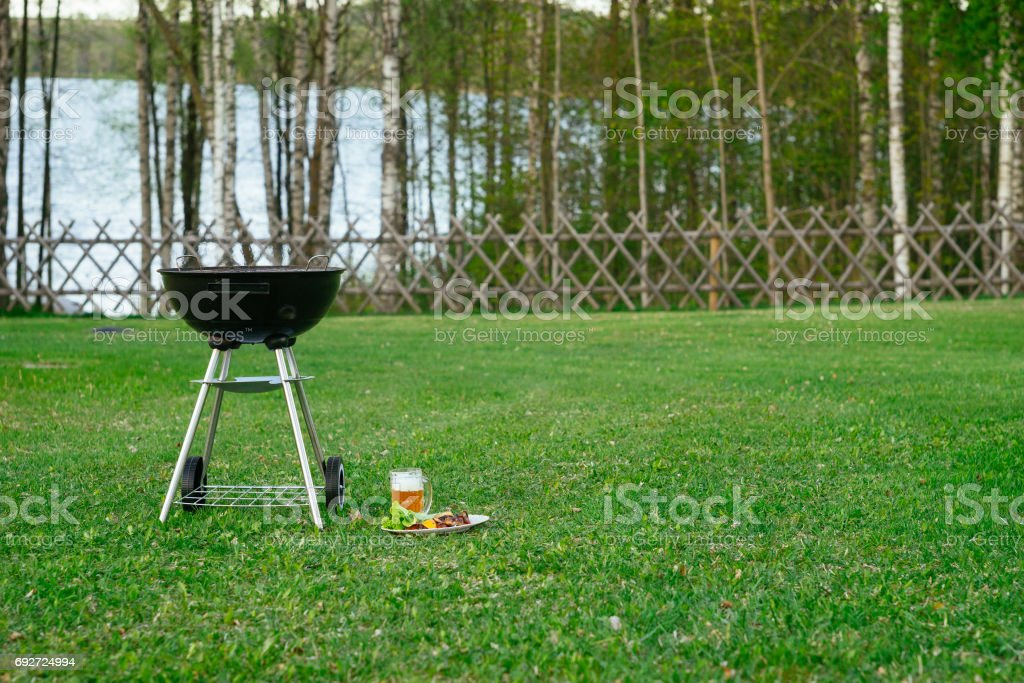 Barbecue grill, beer and grilled vegetables in front of idyllic backyard with lake stock photo