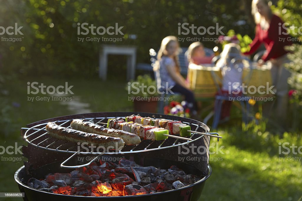 Barbecue grill on a summer evening with family in background stock photo