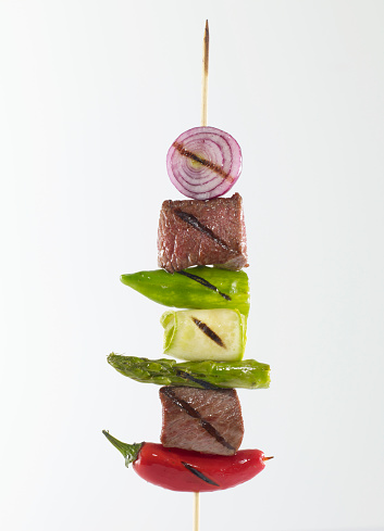 Skewered foods on white background.