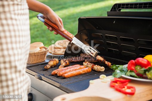 BBQ with different meat, chicken, sausage, hot-dog, souvlaki and more. Bread and vegetables by the side. Putting meat on the plate. Barbecue man with his meat.