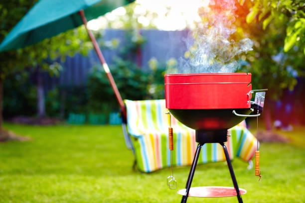 barbecue-grill mit rauch auf hinterhof sommerfest - grillen garten stock-fotos und bilder