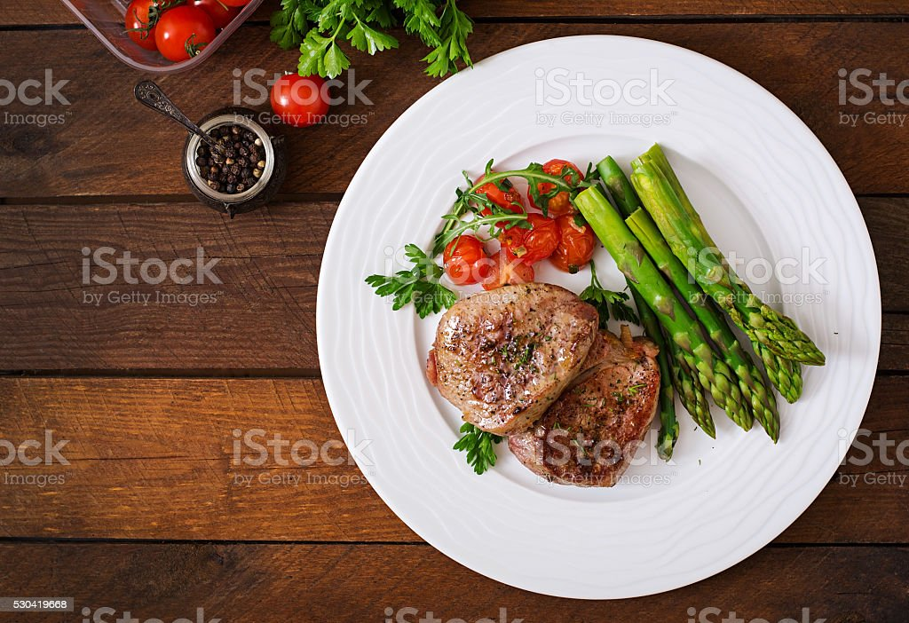 Barbecue grilled beef steak meat with asparagus and tomatoes. stock photo