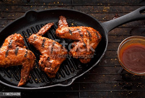 Barbecue grilled chicken wings in a griddle on a dark background