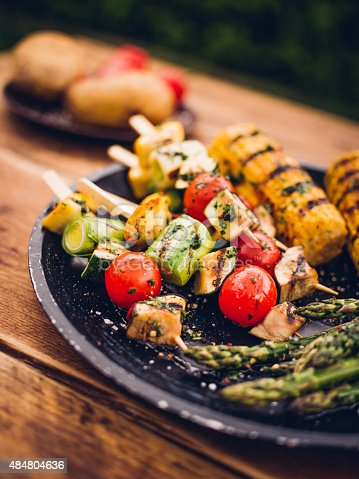 Delicious barbecue grilled vegetable kebabs on a plate with grilled corn and asparagus as a vegetarian option for an outdoor meal