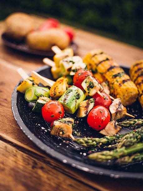 barbecue grilled vegetable kebabs, corn and asparagus on a plate - grilled vegetables stock photos and pictures