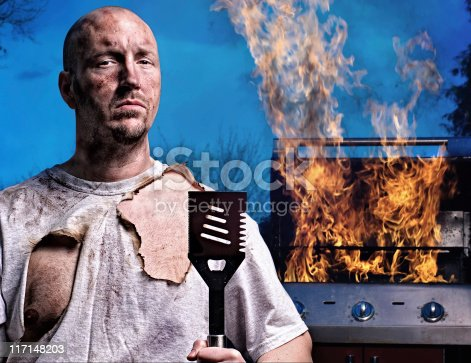 Man with burned face and shirt holding spatula in front of a flaming barbecue grill.