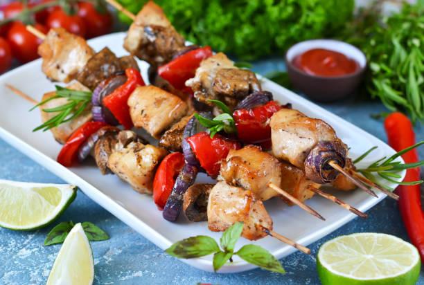 barbecue von huhn auf spießen mit gemüse auf blauem betonhintergrund. picknick. - kebab marinade stock-fotos und bilder