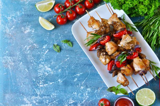 grillen von hähnchen am spieß mit gemüse auf einem blauen konkreten hintergrund. picknick. - kebab marinade stock-fotos und bilder