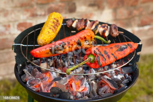 spits of meat, red bell pepper and corncob on a barbecue grill.
