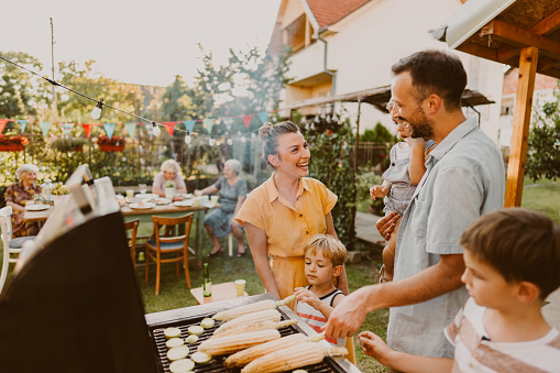 Photo of young family having a barbecue party in their backyard