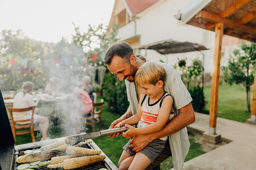 Photo of father showing his boy how to grill